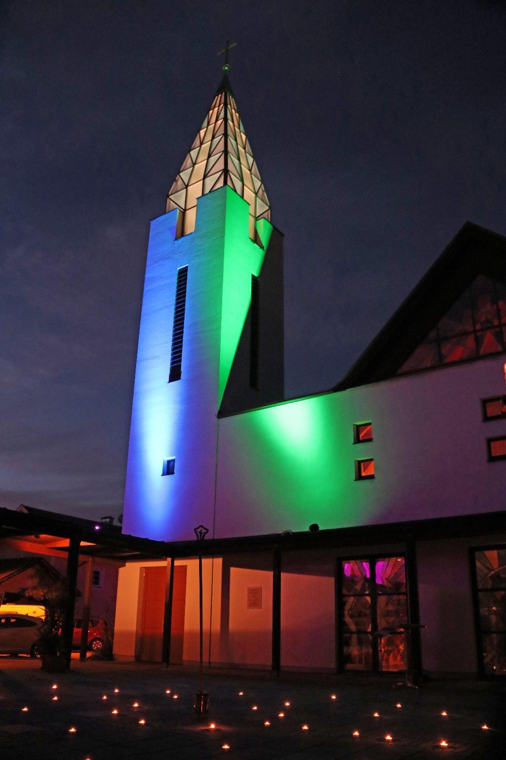Beleuchteter Kirchturm und Pfarrhof mit Kerzen.