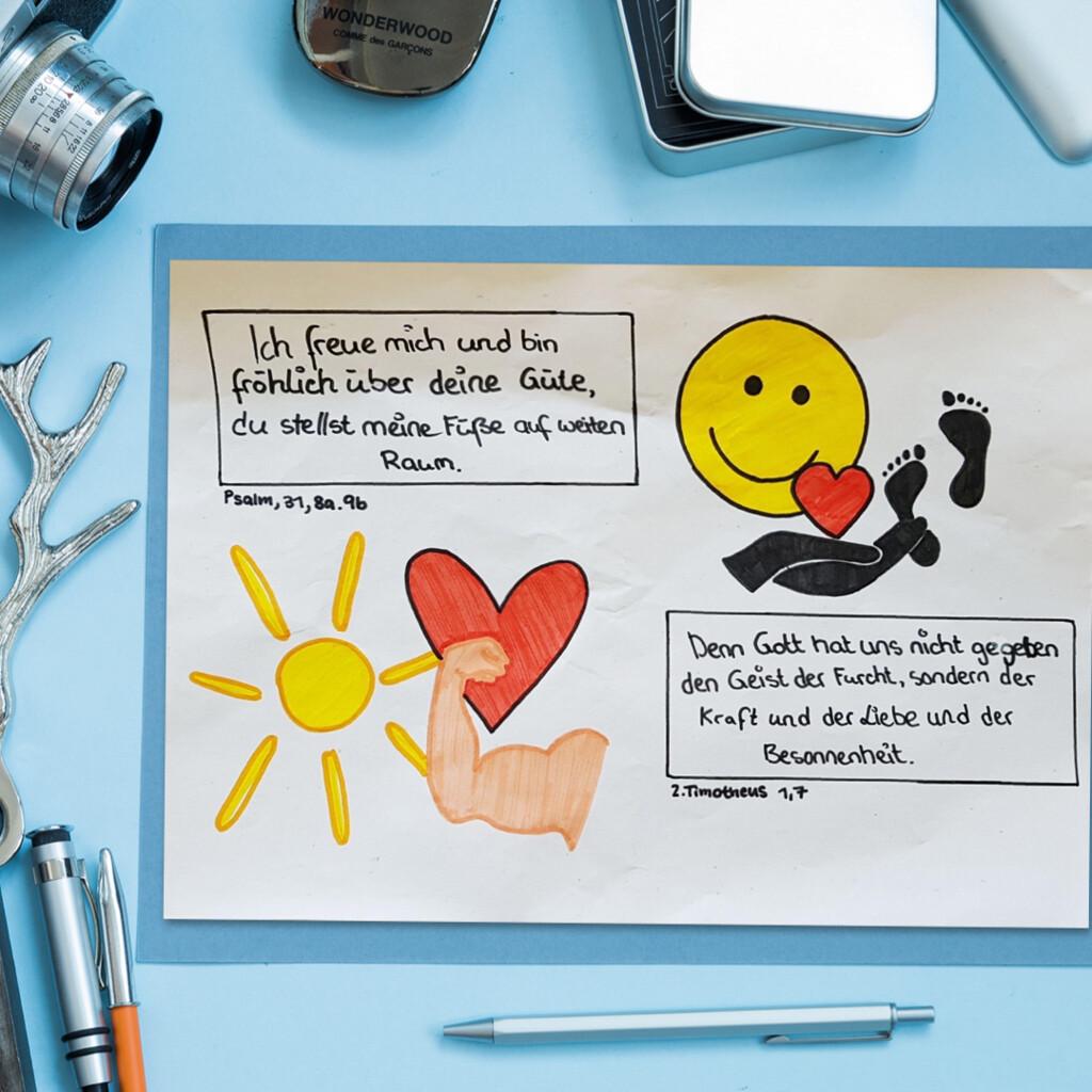 Ein Tisch mit Schreibutensilien, in der Mitte eine Art Plakat mit handgeschriebenen Bibelversen Ps 31, 8,9/ 2.Tim 1,9, daneben Zeichnungen von Jugendlichen, Smiley, Herzen, Fussspuren.