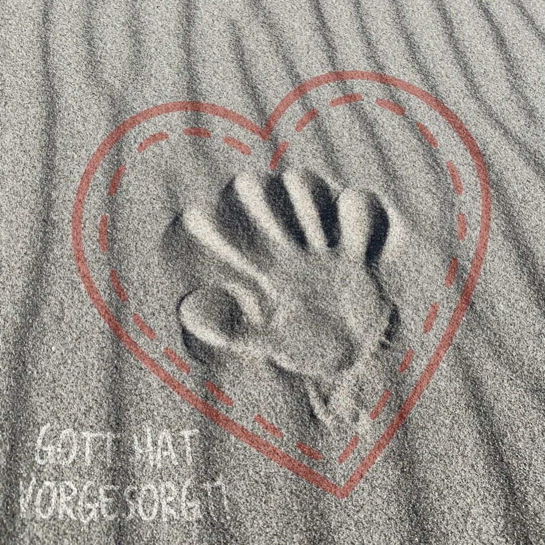 """Handabdruck im Sand mit gemaltem Herz drumherum. Dazu die Worte """"Gott hat vorgesorgt"""" Bildrechte: Kristin Daum"""