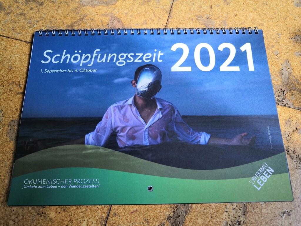 Titelseite des Kalenders: Ein Mann mit weißem Hemd, nass im Meerwasser stehend. Das Gesicht mit einer silbernen Folie, ähnlich einer Maske verdeckt. Vorn schematische grüne Wellen, hinten der Meereshorizont, düster.